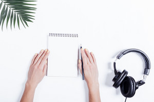 Top view of a female hands with a notebook and pencil, headphones and plant on white table