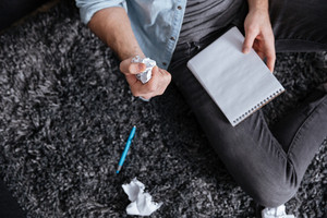 Top view of a man holding crumpled paper and notepad while sitting on carpet