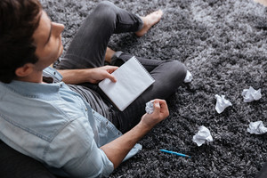 Top view of a pensive man holding crumpled paper and notepad while sitting on carpet