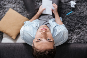 Top view of a pensive young man looking up and holding notepad while sitting on the carpet at home