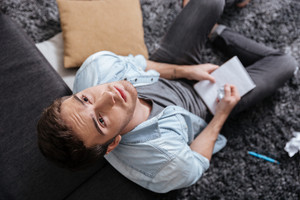 Top view of a thoughtful young man looking up and holding notepad while sitting on the carpet at home