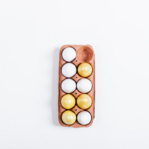Top view of a tray of yellow Easter eggs on white background