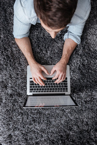 Top view of a young man typing on laptop computer while lying on the carpet at home