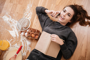 Top view of a young smiling girl talking on mobile phone and cooking breakfast while laying on the floor