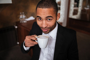 Top view of african man in suit drinking coffee in hotel and looking at camera
