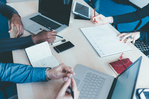Top view of an office desk with a group of people working using technological devices - work, business, teamwork concept