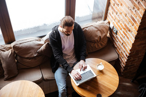 Top view of Bearded man sitting by the table and using laptop in cafe