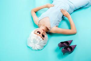 Top view of beautiful blonde young woman lying near her shoes over blue background