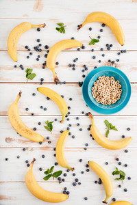 Top view of bowl with cereal, bananas and berries on wooden background