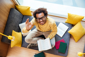 Top view of cheerful african american young man learning and showing ok gesture at home