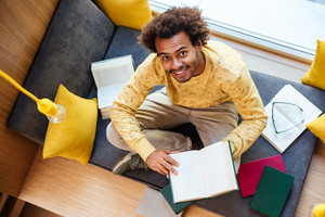 Top view of cheerful african american young man reading book and smiling at home