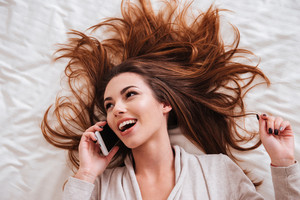 Top view of cheerful playful young woman talking on mobile phone in bed and looking away
