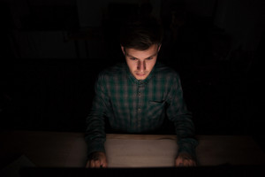 Top view of concentrated young man working with computer at night
