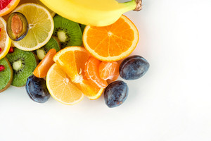 Top view of fresh juicy fruits and citruses over white background