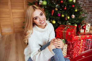 Top view of girl in sweater sitting on the floor near the fir-tree and gifts. looking at camera