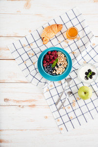 Top view of granola, berries, apple and croissant and plaid napkin on wooden background