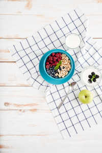 Top view of granola, berries, apple and milk on wooden background