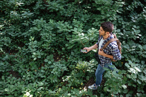 Top view of guy in forest. man with phone, binoculars and backpack. full length image