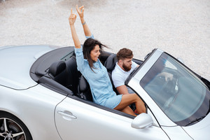 Top view of happy young couple enjoying road trip in their white convertible