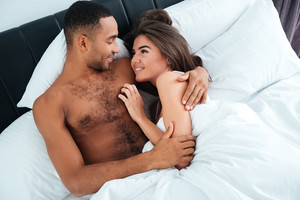 Top view of happy young couple lying and hugging in bed