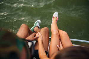 Top view of legs of young couple in sneakers sitting near the sea