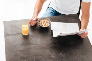 Top view of man with newspaper eating cereals and drinking juice for breakfast at the table