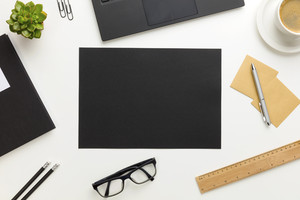 Top view of modern white office desk with black paper in center