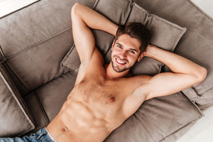 Top view of smiling relaxed young man lying on sofa at home