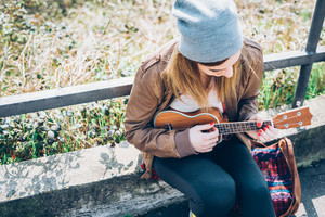 Top view of young beautiful blonde hipster woman sitting outdoor in the city, looking downward playing ukulele - musician, inspiration, composing concept