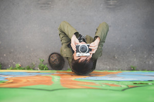 Top view of young handsome caucasian brown short hair woman holding an instant camera, looking upward taking a photograph - creative, photography concept