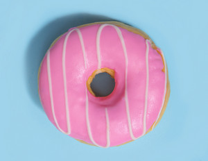 Top view photo of one colorful sweeties donut over blue table background.