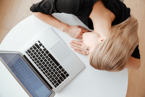 Top view picture of young tired woman worker lies on table in office near laptop computer and sleeping. Eyes closed.