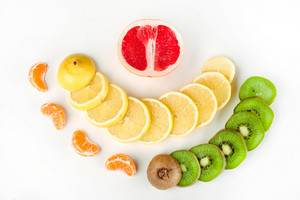 Top view portrait of a composition of fresh sliced citruses and fruits isolated on white background