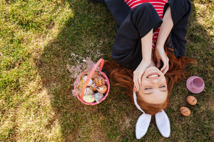 Top view portrait of a smiling happy red head girl wearing easter bunny ears and laying on a grass