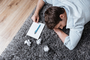 Top view portrait of a tired young man sleeping on carpet with notepad and crumpled paper