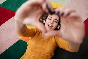 Top view portrait of a young pretty girl in headphones enjoying music while lying on a carpet and showing heart gesture with hands at home