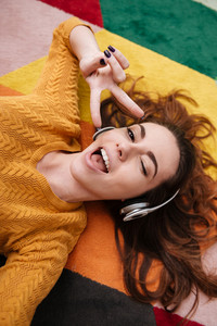 Top view portrait of a young pretty girl in headphones winking and enjoying music while lying on a carpet and showing peace gesture at home