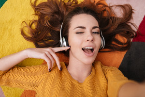 Top view portrait of a young pretty girl in headphones winking and enjoying music while lying on a carpet at home