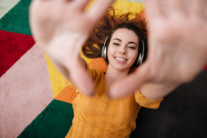 Top view portrait of a young smiling girl in headphones enjoying music while lying on a carpet with outstretched arms at home