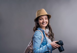 Tourist girl in denim shirt and hat with camera, studio shot on gray background