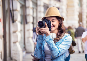 Tourist girl in denim shirt and hat with camera, taking photo, sunny summer day in city