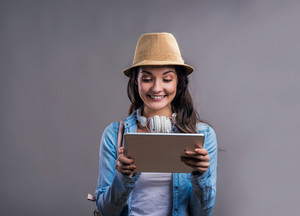 Tourist girl in denim shirt and hat with tablet, studio shot on gray background