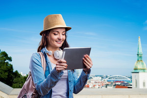 Tourist girl in denim shirt and hat with tablet. Sunny summer day in the city.
