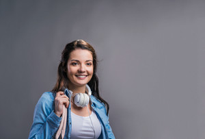 Tourist girl in denim shirt with pink handbag and headphones, studio shot on gray background