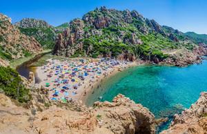 Tourists colorful sun umbrellas at Costa Paradiso Beach, Sardinia, Italy