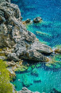 Tourists shorkling between Rocks in Azure Bay of Beautiful Paleokastritsa in Corfu Island, Greece