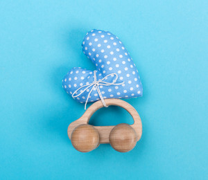 Toy car carrying a heart on a blue background