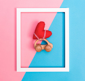 Toy car carrying a heart on a pink and blue background