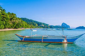 Traditional banca boat in clear water at sandy Corong Beach in El Nido, Philippines