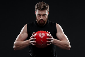 Trainer with ball. holding ball in hands. isolated dark background